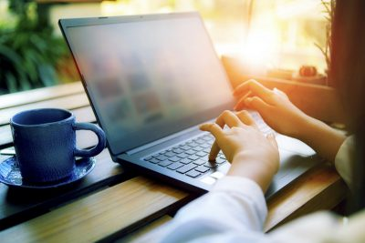 Person working on laptop illustrating how to do affiliate marketing with a website.