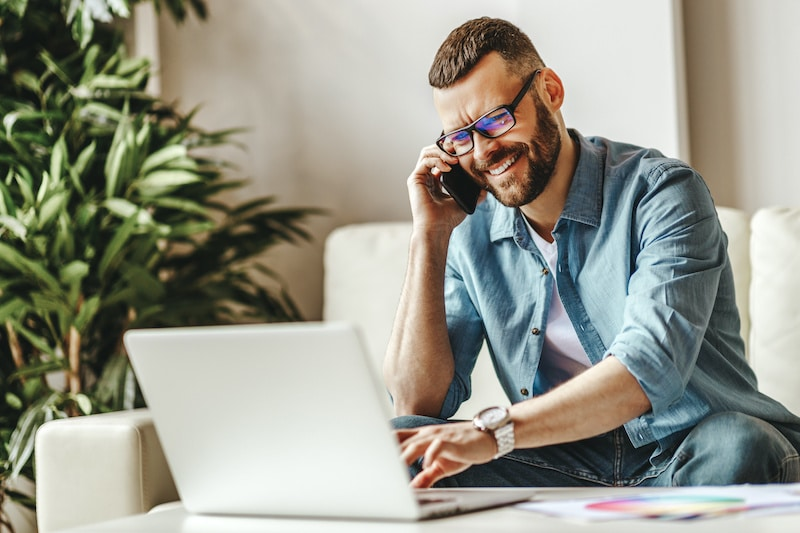 Male freelancer working at home on computer illustrating an alternative home based business model to MLM.