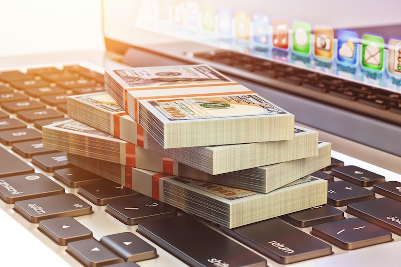 Make money online and internet business concept, bundle of dollar bills on laptop computer keyboard close-up view.