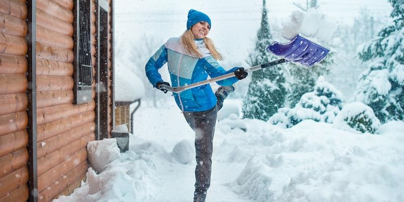 Woman Shoveling Snow Outside House