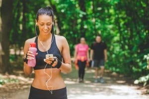 Woman using smartphone app and walking on running track in the park