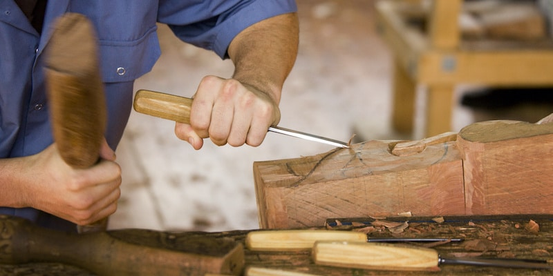 Woodworker crafting furniture out of old wood