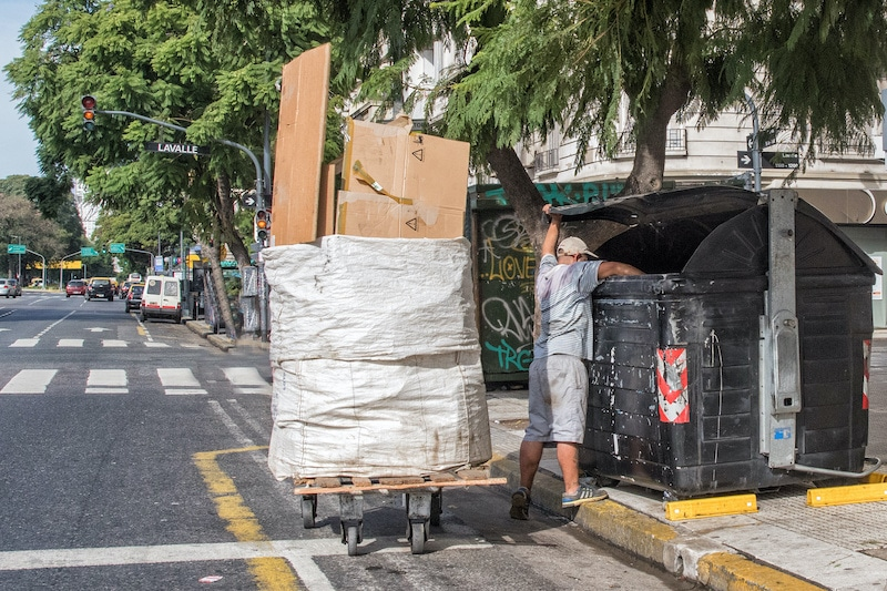 Man searching rubbish bin for items to sell