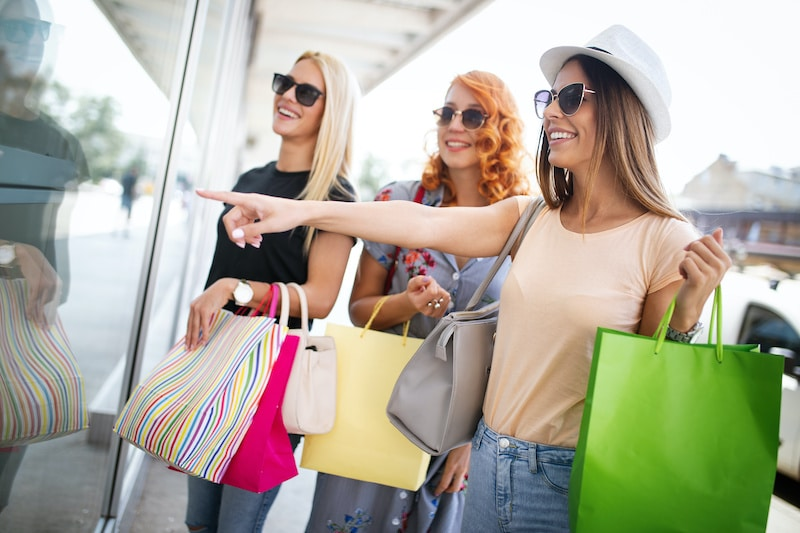 Group of women smiling with handbags