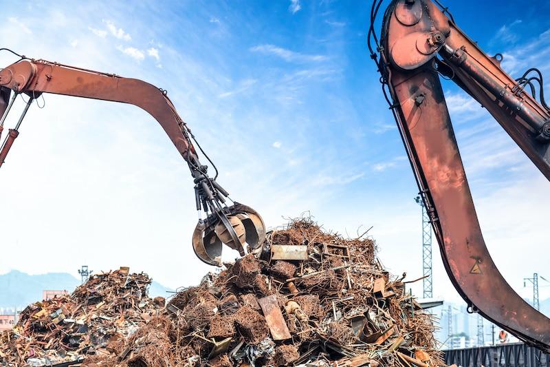 Crane picking up pile of scrap metal
