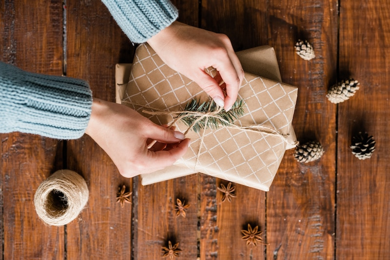 Overview of girl hands binding knot on top of giftbox among pinecones and star anise while packing gifts before holiday