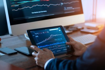 Businessman checking stock market on digital tablet and a desktop computer with stock exchange graph on screen. Financial stock market. Analyzing data in office background