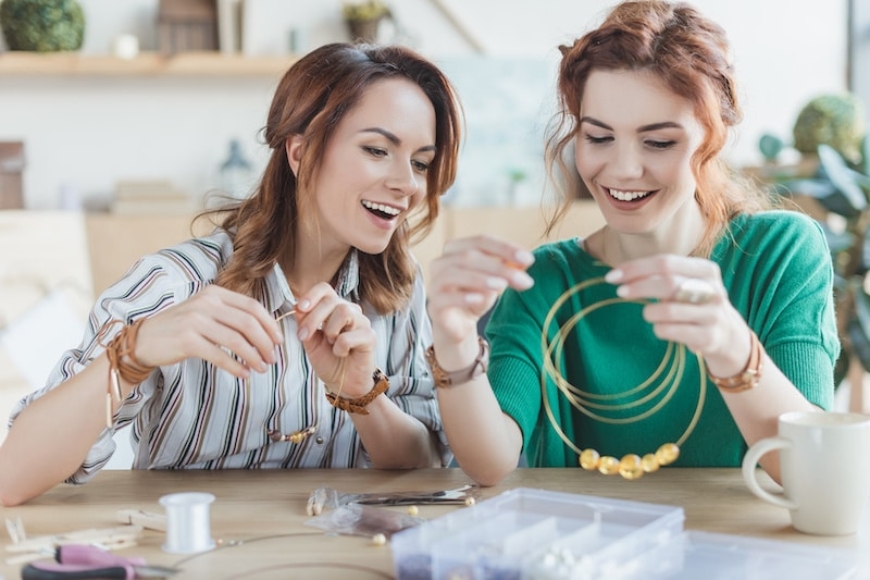 Happy excited women making and assembling crafts in home workshop