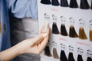 Hair bundles displayed in different colors that are available for purchase against white brick wall.