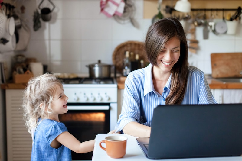 Working mom works from home office on a get paid to site. Happy mother and daughter smiling. Successful woman and cute child using laptop.