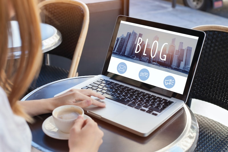 Woman starting an affiliate blog online using laptop computer.