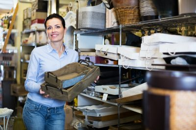 Smiling woman standing with wooden box demonstrating her home decor direct sales business.